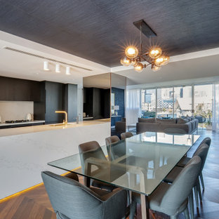 This is an example of a large contemporary galley eat-in kitchen in Sydney with an undermount sink, flat-panel cabinets, dark wood cabinets, white splashback, panelled appliances, medium hardwood floors, with island, brown floor and white benchtop.