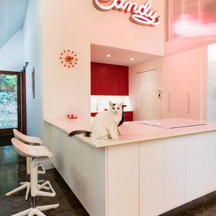 Foto di una cucina ad U minimalista di medie dimensioni con ante lisce, ante rosse, paraspruzzi bianco, paraspruzzi in lastra di pietra, elettrodomestici in acciaio inossidabile, pavimento in cemento, penisola e top bianco