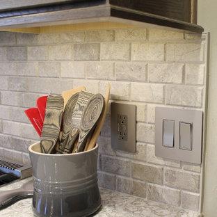 Mittelgroße Klassische Wohnküche in U-Form mit Unterbauwaschbecken, flächenbündigen Schrankfronten, grauen Schränken, Quarzwerkstein-Arbeitsplatte, Küchenrückwand in Grau, Kalk-Rückwand, Küchengeräten aus Edelstahl, Keramikboden, Kücheninsel, grauem Boden und grauer Arbeitsplatte in Sonstige