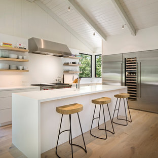 Large mid-century modern kitchen inspiration - Example of a large 1960s l-shaped light wood floor and beige floor kitchen design in Other with open cabinets, white backsplash, stainless steel appliances, an island, an undermount sink, white cabinets and quartz countertops
