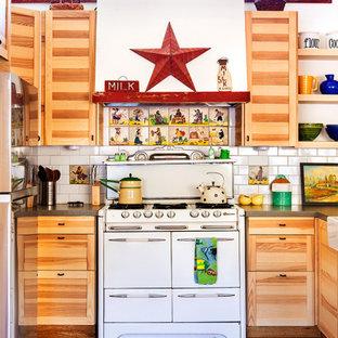 他の地域の中くらいのエクレクティックスタイルのおしゃれなキッチン (エプロンフロントシンク、シェーカースタイル扉のキャビネット、淡色木目調キャビネット、珪岩カウンター、白いキッチンパネル、サブウェイタイルのキッチンパネル、白い調理設備、淡色無垢フローリング、グレーのキッチンカウンター) の写真