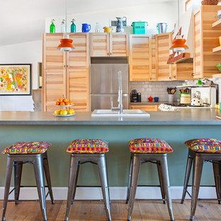 他の地域の広いエクレクティックスタイルのおしゃれなキッチン (シェーカースタイル扉のキャビネット、淡色木目調キャビネット、珪岩カウンター、白いキッチンパネル、サブウェイタイルのキッチンパネル、グレーのキッチンカウンター、ドロップインシンク、シルバーの調理設備、無垢フローリング、茶色い床、三角天井) の写真