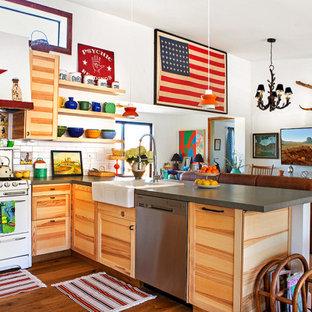 他の地域の広いエクレクティックスタイルのおしゃれなキッチン (エプロンフロントシンク、シェーカースタイル扉のキャビネット、淡色木目調キャビネット、珪岩カウンター、白いキッチンパネル、サブウェイタイルのキッチンパネル、白い調理設備、淡色無垢フローリング、グレーのキッチンカウンター) の写真