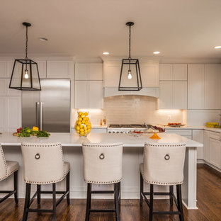 Large transitional l-shaped dark wood floor eat-in kitchen photo in DC Metro with a farmhouse sink, shaker cabinets, white cabinets, beige backsplash, stainless steel appliances, an island, quartz countertops and porcelain backsplash