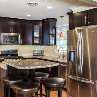 Mid-sized contemporary eat-in kitchen photos - Eat-in kitchen - mid-sized contemporary l-shaped medium tone wood floor and orange floor eat-in kitchen idea in Other with an undermount sink, flat-panel cabinets, dark wood cabinets, granite countertops, glass tile backsplash, stainless steel appliances, an island and multicolored backsplash