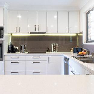 Mittelgroße Industrial Wohnküche in U-Form mit Einbauwaschbecken, flächenbündigen Schrankfronten, weißen Schränken, Kupfer-Arbeitsplatte, Küchenrückwand in Weiß, Glasrückwand, weißen Elektrogeräten, braunem Holzboden, Kücheninsel, weißem Boden und weißer Arbeitsplatte in Brisbane