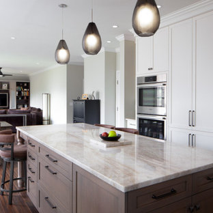 Design ideas for a large tropical u-shaped open plan kitchen in Raleigh with a double-bowl sink, shaker cabinets, white cabinets, quartzite benchtops, blue splashback, glass tile splashback, stainless steel appliances, dark hardwood floors, with island, brown floor and white benchtop.