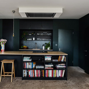 Inspiration for a medium sized traditional kitchen in London with flat-panel cabinets, black cabinets, wood worktops, black splashback, concrete flooring, an island, grey floors and a single-bowl sink.