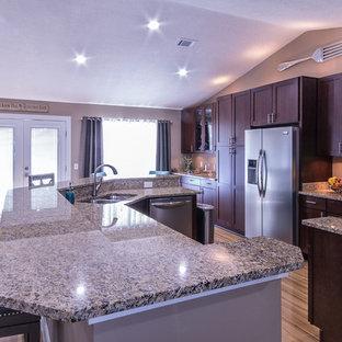 Diseño de cocina en L, clásica renovada, de tamaño medio, abierta, con fregadero bajoencimera, armarios estilo shaker, puertas de armario de madera en tonos medios, encimera de granito, electrodomésticos de acero inoxidable, suelo de madera clara y una isla
