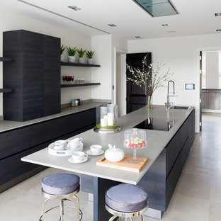 This is an example of a medium sized contemporary single-wall kitchen in London with a submerged sink, flat-panel cabinets, blue cabinets, quartz worktops, integrated appliances, an island, beige floors and grey worktops.
