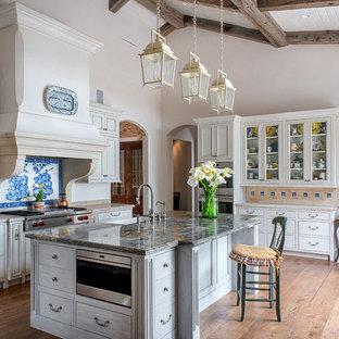 Idéer för avskilda, stora lantliga beige l-kök, med luckor med glaspanel, beige skåp, flerfärgad stänkskydd, rostfria vitvaror, ljust trägolv, en köksö, en rustik diskho, bänkskiva i kvartsit, stänkskydd i keramik och brunt golv