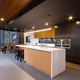 Inspiration for a contemporary galley eat-in kitchen in Brisbane with flat-panel cabinets, black cabinets, stainless steel appliances, with island and grey floor.
