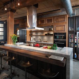 トロントのインダストリアルスタイルのおしゃれなキッチン (アンダーカウンターシンク、レイズドパネル扉のキャビネット、中間色木目調キャビネット、コンクリートの床、シルバーの調理設備) の写真