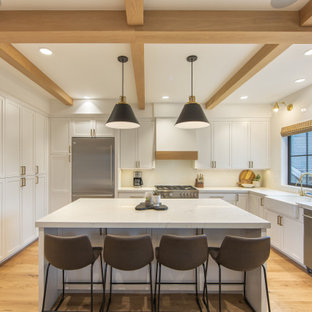 Пример оригинального дизайна: п-образная кухня-гостиная среднего размера в современном стиле с раковиной в стиле кантри, фасадами в стиле шейкер, белыми фасадами, столешницей из кварцевого агломерата, белым фартуком, фартуком из плитки кабанчик, техникой из нержавеющей стали, светлым паркетным полом, островом, коричневым полом, белой столешницей и кессонным потолком