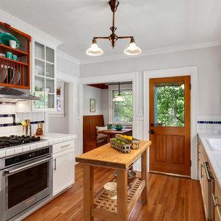 シアトルのおしゃれなキッチン (ダブルシンク、ガラス扉のキャビネット、白いキャビネット、タイルカウンター、マルチカラーのキッチンパネル、シルバーの調理設備の、無垢フローリング、白いキッチンカウンター) の写真