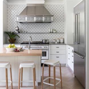 Diseño de cocina en L, tradicional renovada, con armarios con paneles empotrados, puertas de armario blancas, salpicadero blanco, electrodomésticos de acero inoxidable, suelo de madera clara, una isla, suelo beige y encimeras grises