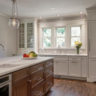Idéer för att renovera ett stort amerikanskt vit vitt kök, med en undermonterad diskho, skåp i shakerstil, vita skåp, beige stänkskydd, rostfria vitvaror, mörkt trägolv, en köksö, stänkskydd i tunnelbanekakel, marmorbänkskiva och brunt golv