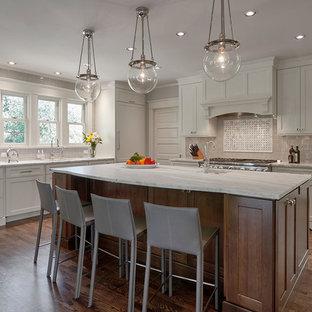 シアトルの大きいおしゃれなキッチン (アンダーカウンターシンク、シェーカースタイル扉のキャビネット、白いキャビネット、ベージュキッチンパネル、セラミックタイルのキッチンパネル、シルバーの調理設備の、濃色無垢フローリング、大理石カウンター、茶色い床、白いキッチンカウンター) の写真