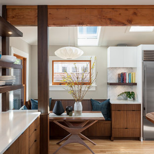 Inspiration for a mid-sized midcentury l-shaped eat-in kitchen in Seattle with an undermount sink, medium wood cabinets, quartz benchtops, white splashback, stone tile splashback, stainless steel appliances and medium hardwood floors.