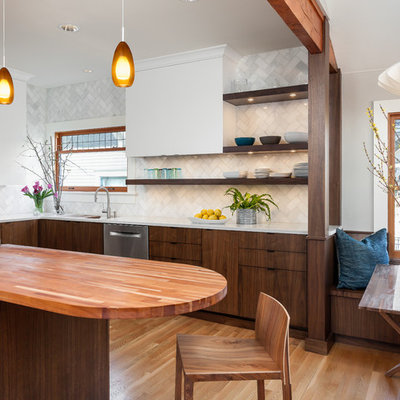 Example of a mid-sized 1950s l-shaped medium tone wood floor eat-in kitchen design in Seattle with quartz countertops, white backsplash, stone tile backsplash, stainless steel appliances, a double-bowl sink, dark wood cabinets, an island and flat-panel cabinets