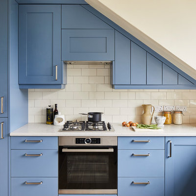 Transitional l-shaped kitchen photo in London with shaker cabinets, blue cabinets, white backsplash, subway tile backsplash, stainless steel appliances and white countertops