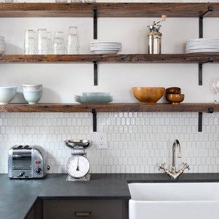 フィラデルフィアの中くらいのエクレクティックスタイルのおしゃれなキッチン (エプロンフロントシンク、フラットパネル扉のキャビネット、グレーのキャビネット、白いキッチンパネル、セラミックタイルのキッチンパネル、シルバーの調理設備、磁器タイルの床、アイランドなし、マルチカラーの床) の写真