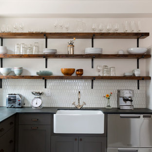 Inspiration for a mid-sized contemporary l-shaped eat-in kitchen in Philadelphia with a farmhouse sink, grey cabinets, white splashback, ceramic splashback, stainless steel appliances, porcelain floors, no island, multi-coloured floor, shaker cabinets and grey benchtop.