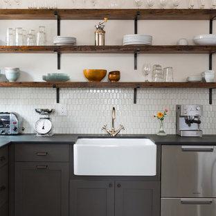 フィラデルフィアの中サイズのエクレクティックスタイルのおしゃれなキッチン (エプロンフロントシンク、フラットパネル扉のキャビネット、グレーのキャビネット、白いキッチンパネル、セラミックタイルのキッチンパネル、シルバーの調理設備の、磁器タイルの床、アイランドなし、マルチカラーの床) の写真