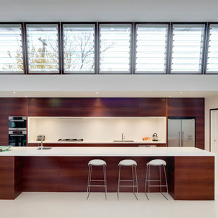Example of a trendy single-wall kitchen design in Sydney with flat-panel cabinets, dark wood cabinets, white backsplash and stainless steel appliances