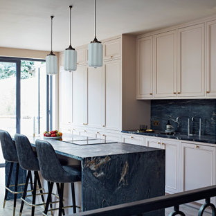 Contemporary galley eat-in kitchen in London with an integrated sink, recessed-panel cabinets, pink cabinets, marble benchtops, black splashback, marble splashback, light hardwood floors, with island and black benchtop.