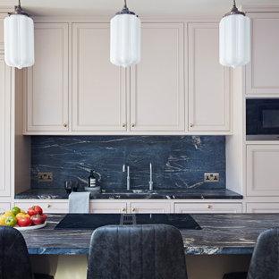 Aménagement d'une cuisine américaine parallèle contemporaine avec un évier intégré, un placard avec porte à panneau encastré, des portes de placard rose, un plan de travail en marbre, une crédence noire, une crédence en marbre, un îlot central et un plan de travail noir.