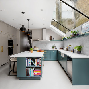 Large contemporary u-shaped eat-in kitchen in London with a farmhouse sink, green cabinets, quartzite benchtops, marble splashback, stainless steel appliances, porcelain floors, with island, grey floor, white benchtop, flat-panel cabinets and grey splashback.