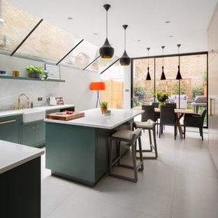 ロンドンの広いコンテンポラリースタイルのおしゃれなキッチン (エプロンフロントシンク、緑のキャビネット、珪岩カウンター、マルチカラーのキッチンパネル、大理石のキッチンパネル、シルバーの調理設備、磁器タイルの床、グレーの床、白いキッチンカウンター) の写真