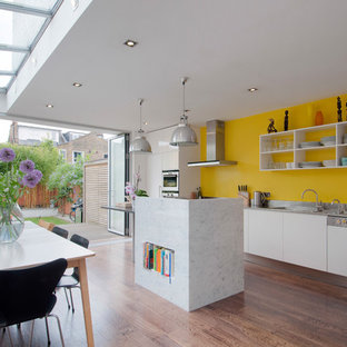 Inspiration for a contemporary kitchen/diner in London with an integrated sink, white cabinets, stainless steel worktops, yellow splashback, integrated appliances, dark hardwood flooring, an island, brown floors and open cabinets.