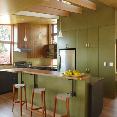 Example of a mid-sized trendy l-shaped medium tone wood floor and brown floor open concept kitchen design in San Francisco with flat-panel cabinets, green cabinets, green backsplash, stainless steel appliances, wood countertops, glass tile backsplash and an island
