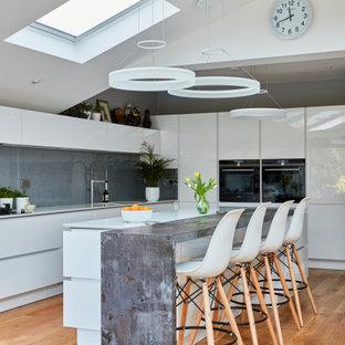 ロンドンの広いコンテンポラリースタイルのおしゃれなキッチン (フラットパネル扉のキャビネット、白いキャビネット、御影石カウンター、グレーのキッチンパネル、茶色い床、白いキッチンカウンター、黒い調理設備、無垢フローリング、三角天井) の写真