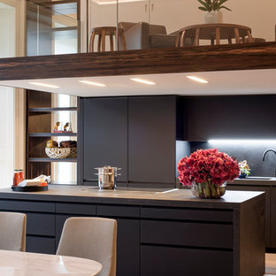 Photo of an expansive midcentury galley open plan kitchen in London with a drop-in sink, glass-front cabinets, black cabinets, glass benchtops, black splashback, porcelain splashback, panelled appliances, with island and black benchtop.