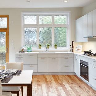 バンクーバーの小さいモダンスタイルのおしゃれなキッチン (アンダーカウンターシンク、フラットパネル扉のキャビネット、黄色いキャビネット、珪岩カウンター、白いキッチンパネル、セラミックタイルのキッチンパネル、パネルと同色の調理設備、淡色無垢フローリング) の写真