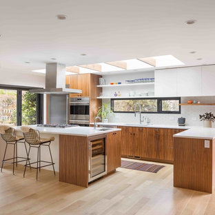 Midcentury l-shaped kitchen in Portland with an undermount sink, flat-panel cabinets, medium wood cabinets, white splashback, stainless steel appliances, light hardwood floors, with island, beige floor and white benchtop.