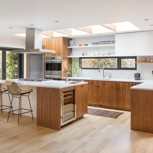 This is an example of a mid-sized midcentury l-shaped kitchen in Portland with an undermount sink, flat-panel cabinets, quartz benchtops, white splashback, ceramic splashback, stainless steel appliances, light hardwood floors, with island, white benchtop, white cabinets and beige floor.