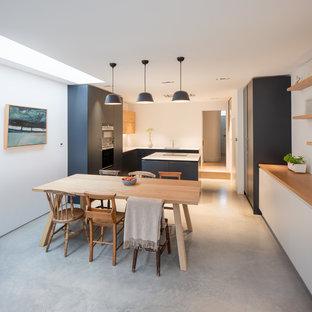ロンドンの大きい北欧スタイルのおしゃれなキッチン (ドロップインシンク、フラットパネル扉のキャビネット、グレーのキャビネット、珪岩カウンター、パネルと同色の調理設備、コンクリートの床、グレーの床、白いキッチンカウンター) の写真