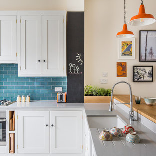This is an example of a small transitional l-shaped kitchen in London with a farmhouse sink, shaker cabinets, white cabinets, quartz benchtops, blue splashback, subway tile splashback, stainless steel appliances, ceramic floors and multi-coloured floor.