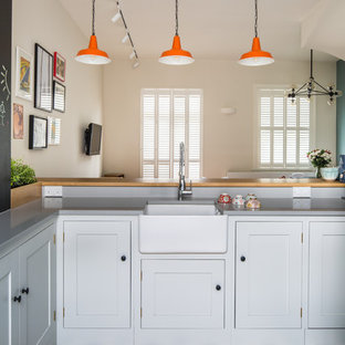 Small contemporary l-shaped open plan kitchen in London with a farmhouse sink, shaker cabinets, white cabinets, quartz benchtops, blue splashback, subway tile splashback, stainless steel appliances, ceramic floors, a peninsula and multi-coloured floor.
