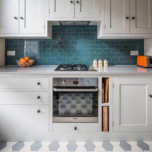 Idéer för ett litet modernt kök, med en rustik diskho, skåp i shakerstil, vita skåp, bänkskiva i kvarts, blått stänkskydd, stänkskydd i tunnelbanekakel, rostfria vitvaror, klinkergolv i keramik, en halv köksö och flerfärgat golv