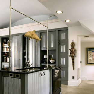 Photo of a mid-sized industrial galley eat-in kitchen in Atlanta with a double-bowl sink, black appliances, stainless steel cabinets, granite benchtops, concrete floors and with island.