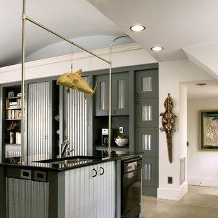 Idées déco pour une cuisine américaine parallèle industrielle de taille moyenne avec un évier 2 bacs, un électroménager noir, une façade en inox, un plan de travail en granite, béton au sol et un îlot central.