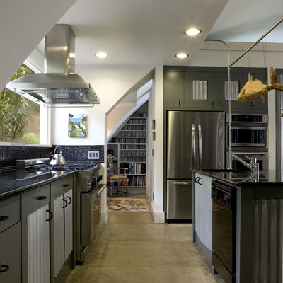Inspiration for a mid-sized industrial galley concrete floor eat-in kitchen remodel in Atlanta with stainless steel appliances, an undermount sink, granite countertops, black backsplash, glass tile backsplash, an island and gray cabinets