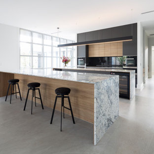 This is an example of a contemporary galley open plan kitchen in Canberra - Queanbeyan with flat-panel cabinets, black cabinets, black appliances, multiple islands, grey floor and grey benchtop.