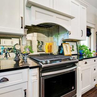 マイアミの大きいシャビーシック調のおしゃれなキッチン (アンダーカウンターシンク、落し込みパネル扉のキャビネット、白いキャビネット、御影石カウンター、メタリックのキッチンパネル、ミラータイルのキッチンパネル、シルバーの調理設備の、黒いキッチンカウンター、クッションフロア、茶色い床) の写真