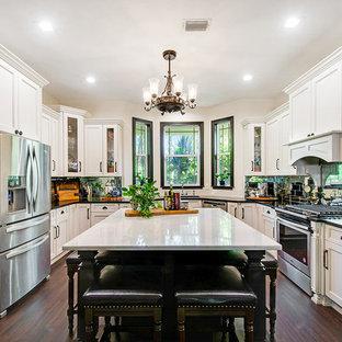 Große Shabby-Style Wohnküche in U-Form mit Unterbauwaschbecken, Schrankfronten mit vertiefter Füllung, gelben Schränken, Granit-Arbeitsplatte, Küchenrückwand in Metallic, Rückwand aus Spiegelfliesen, Küchengeräten aus Edelstahl, Vinylboden, Kücheninsel, braunem Boden und schwarzer Arbeitsplatte in Miami